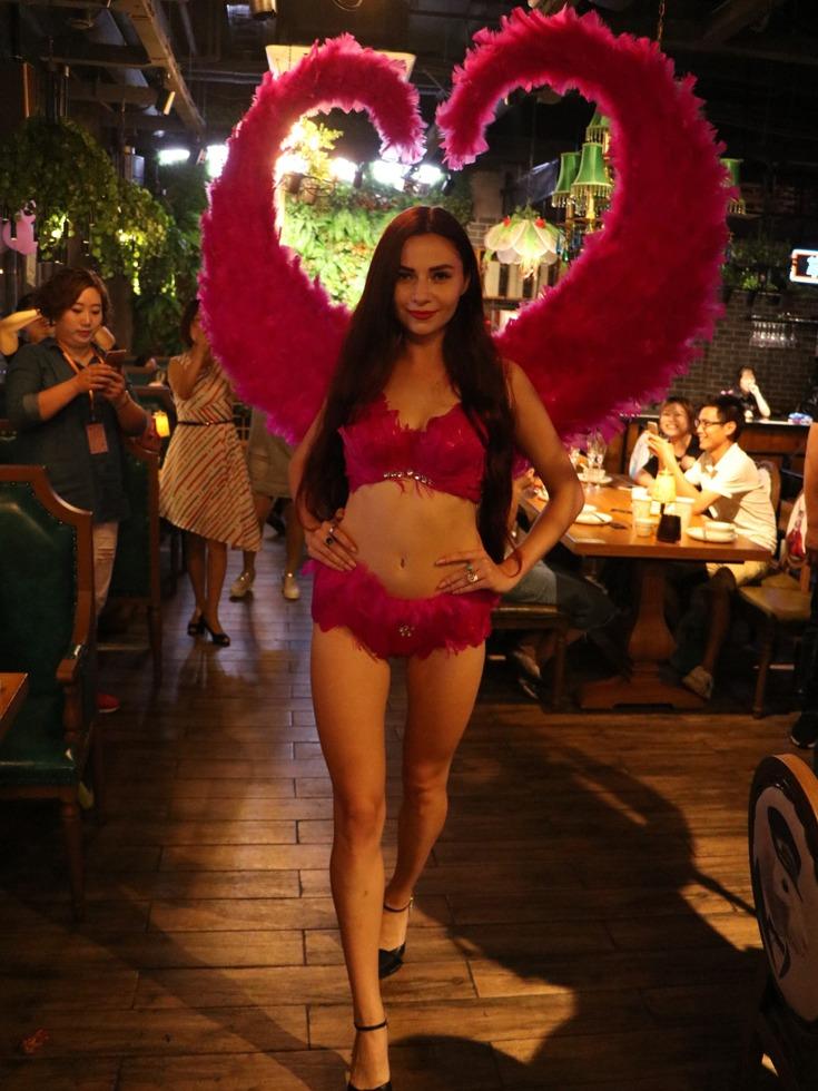 外籍超模背着红色的大翅膀为食客们表演。(图源:VCG)