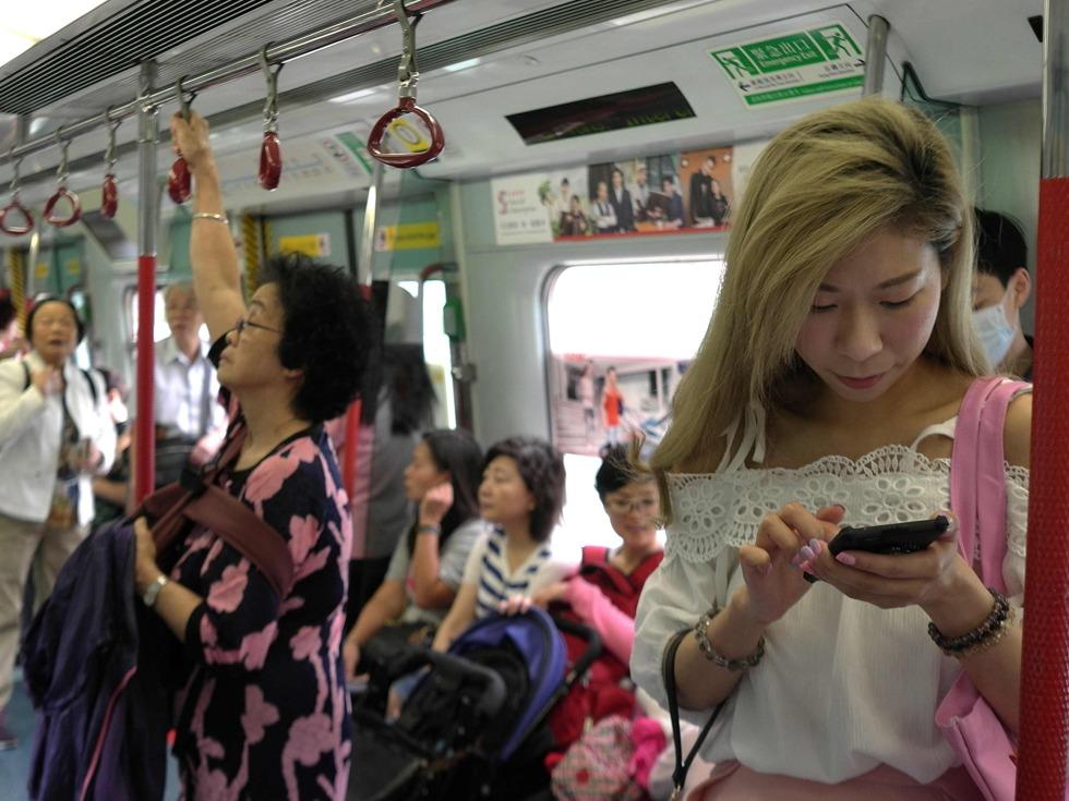 地铁文化在迪士尼线也表现得淋漓尽致,香港地铁迪士尼线是专为迪士尼主题公园而设的铁路专线,迪士尼列车车窗设计为米老鼠头形状,车厢外部点缀金色彩带以及奇妙星粉图案。图为2017年5月18日,人们乘坐地铁出行。一位时尚女性在使用智能手机。(图源:VCG)